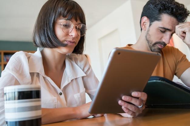 自宅からデジタルタブレットで請求書を計算して支払う若いカップルの肖像画。毎月の予算を計画しているカップル。