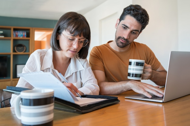 自宅からラップトップで請求書を計算して支払う若いカップルの肖像画