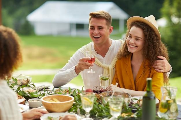 夏のパーティーで屋外の友人と飲み物を持ってテーブルに座って夕食を楽しみながら抱きしめる若いカップルの肖像画