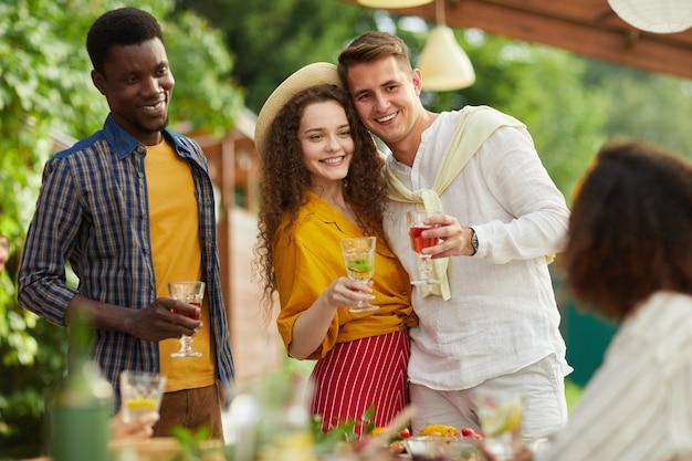 Портрет молодой пары, обнимающейся, стоя за столом и ужинающей с друзьями на открытом воздухе на летней вечеринке