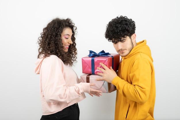 Портрет молодой пары, обменивающейся подарками на ранний праздник над белой стеной.