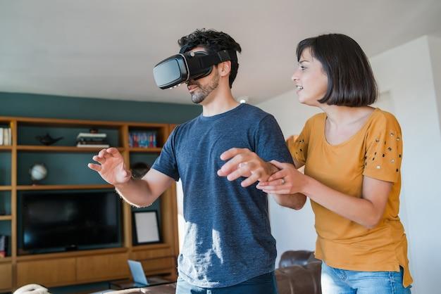 一緒に楽しんで、家にいる間vrメガネでビデオゲームをプレイする若いカップルの肖像画。新しい通常のライフスタイルのコンセプト。