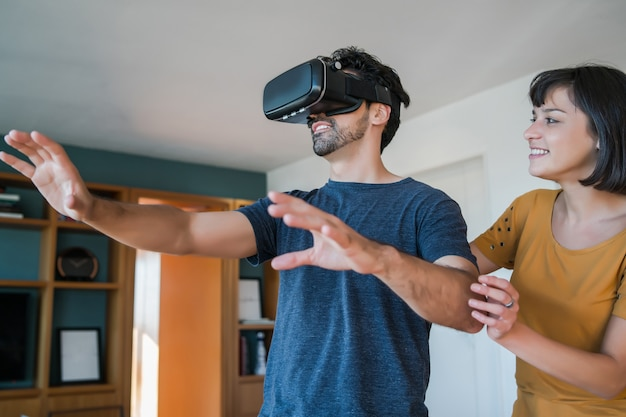 Портрет молодой пары, весело проводящей время вместе и играя в видеоигры с очками vr, оставаясь дома. новая концепция нормального образа жизни.
