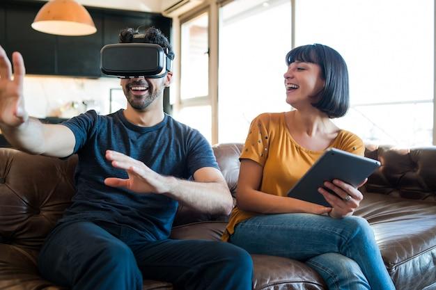 Портрет молодой пары, весело проводящей время вместе и играя в видеоигры в очках vr, оставаясь дома