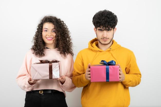 Портрет молодой пары, держащей подарочные коробки над белой стеной.