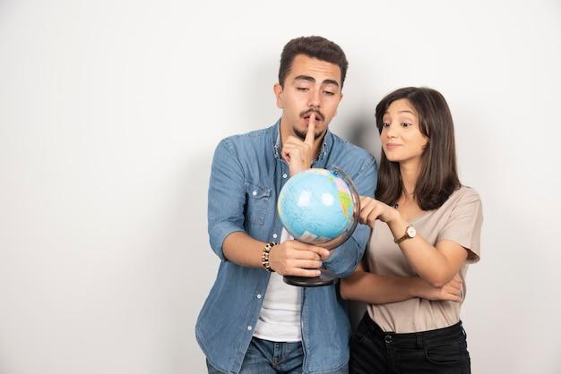 Портрет молодой пары, держащей глобус карты.
