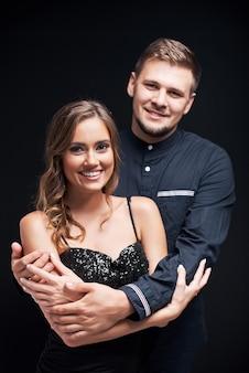 黒に対して抱いて若いカップルの肖像画