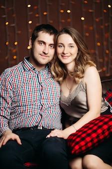家で抱き締める若いカップルの肖像画