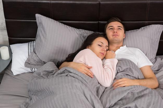 ベッドで寝ている間、灰色のロフトスタイルで寝室でパジャマを着ている間、お互いを抱き締める若いカップルの肖像画