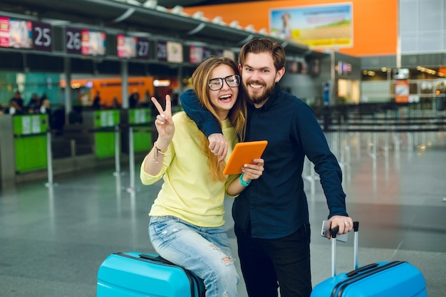 공항에서 포옹하는 젊은 부부의 초상화입니다. 그녀는 긴 머리, 노란색 스웨터, 청바지 및 태블릿을 가지고 있습니다. 근처에 검은 색 셔츠, 바지, 여행 가방이 있습니다. 그들은 카메라에 웃고 있습니다.