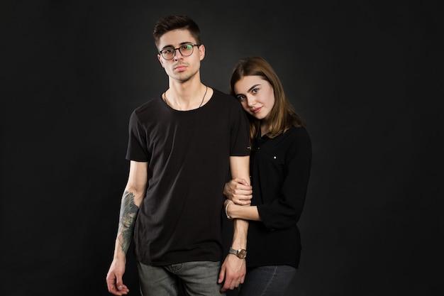 검은 옷을 입고 트렌디 한 안경을 쓰고 검은 배경 위에 포즈를 취하는 젊은 부부의 초상화.