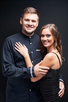 黒に分離されたエレガントな夜服の若いカップルの肖像画