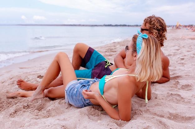 ビーチで恋をし、一緒に時間を楽しんでいる若いカップルの肖像画