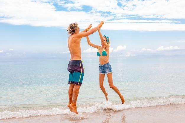 해변에서 포용과 함께 시간을 즐기고 사랑에 젊은 부부의 초상화. 모래 해안에 재미 젊은 부부