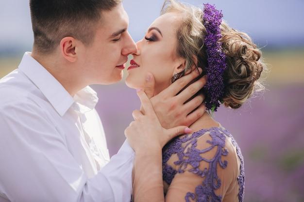 Портрет молодой влюбленной пары, целующейся в лавандовом поле летом