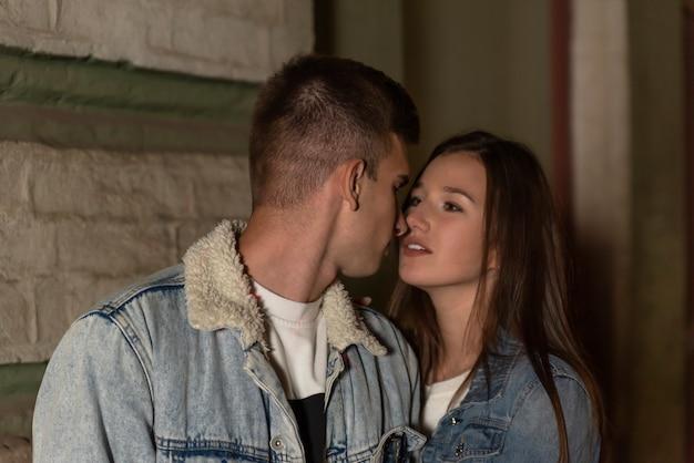 お互いを見ている愛の若いカップルの肖像画。夜のロマンチックなデートの若いカップル。夜の街。