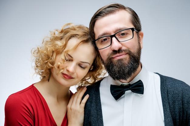 古典的な服を着てスタジオでポーズをとって恋に若いカップルの肖像画。閉じる