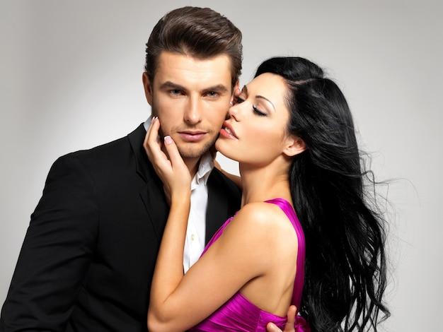 古典的な服を着てスタジオでポーズをとって恋に若いカップルの肖像