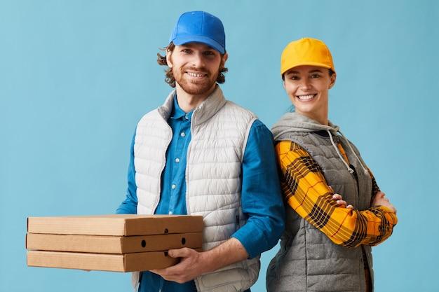 Портрет молодой пары в униформе, доставляющей пиццу и улыбающейся в камеру на синем фоне