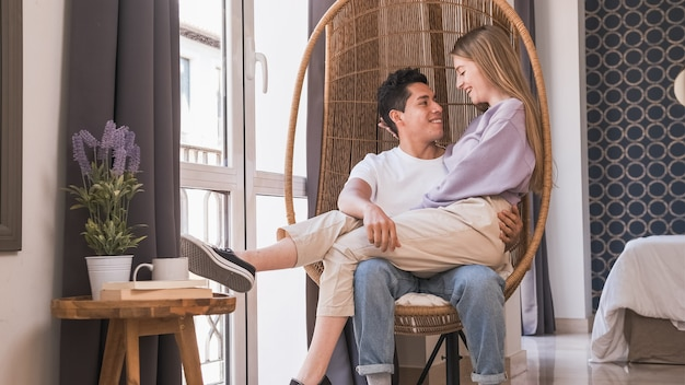 집에서 함께 고리 버들 의자에 앉아있는 동안 서로를 찾고 젊은 부부의 초상화