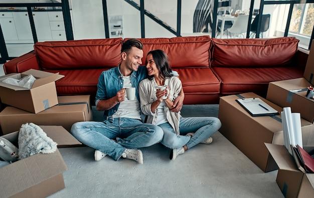 차 또는 커피 머그잔을 들고 앉아 새 집으로 이사하는 젊은 부부의 초상화. 이사, 집 구입, 아파트 개념.