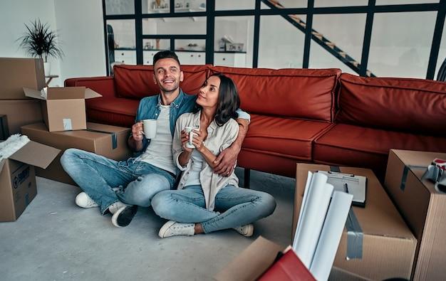 Портрет молодой пары, переезжающей в новый дом, сидя с кружками чая или кофе. переезд, покупка дома, концепция квартиры.