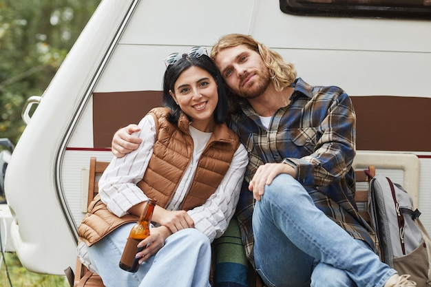 トレーラーバンでキャンプし、カメラのコピーを見ながら屋外でリラックスする若いカップルの肖像画...