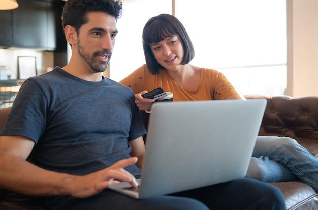 自宅からクレジットカードとラップトップでオンラインショッピングをする若いカップルの肖像画。 eコマースの概念。新しい通常のライフスタイル。
