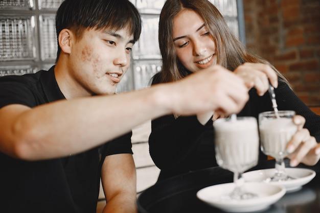 カプチーノを手にレストランに座っている若いカップルの肖像画。黒髪の白人の女の子と黒髪のアジア人の男の子が一緒に座っています。黒のtシャツを着ている男の子と女の子。