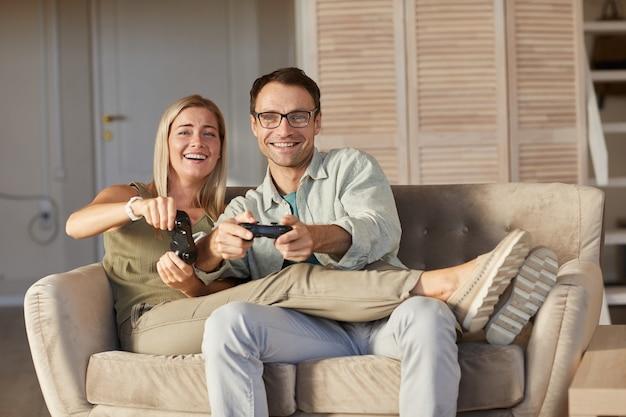 自宅でコンピュータゲームで遊んで楽しんでいる間カメラで笑っている若いカップルの肖像画