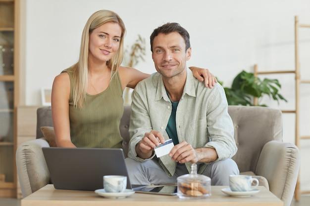 ラップトップコンピューターを使用してクレジットカードでオンライン購入の支払いをしながらカメラに微笑んでいる若いカップルの肖像画