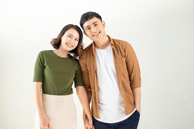 白い壁に笑みを浮かべて若いカップルの肖像画