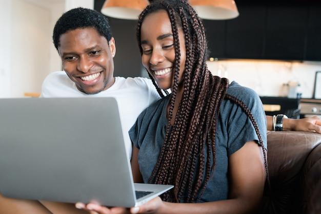 一緒に時間を過ごし、自宅のソファに座ってラップトップを使用して若いカップルの肖像画。