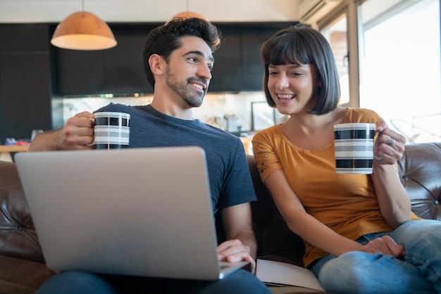 Портрет молодой пары, проводящей время вместе и использующей ноутбук, сидя на диване у себя дома
