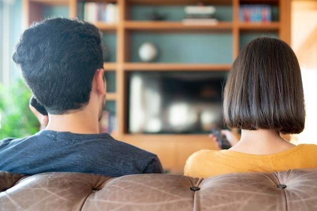一緒に時間を過ごし、自宅のソファに座ってテレビシリーズや映画を見ている若いカップルの肖像画。新しい通常のライフスタイルのコンセプト。