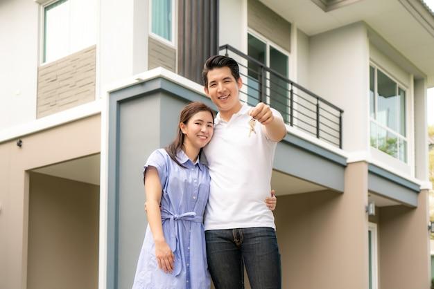 Портрет молодой пары, стоящей и обнимающейся вместе и держащей ключ от дома