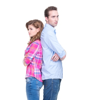 Портрет молодой пары, стоящей спиной к спине и мышления, изолированной на белой стене.