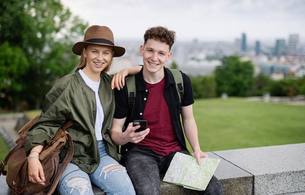 카메라를 보고 휴가에 도시에서 지도와 젊은 부부 여행자의 초상화.