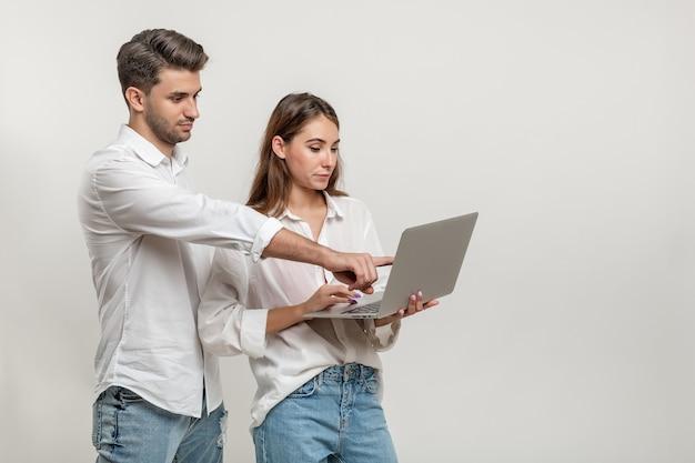 흰색 배경에 격리된 화면을 가리키는 노트북을 사용하는 젊은 부부의 초상화