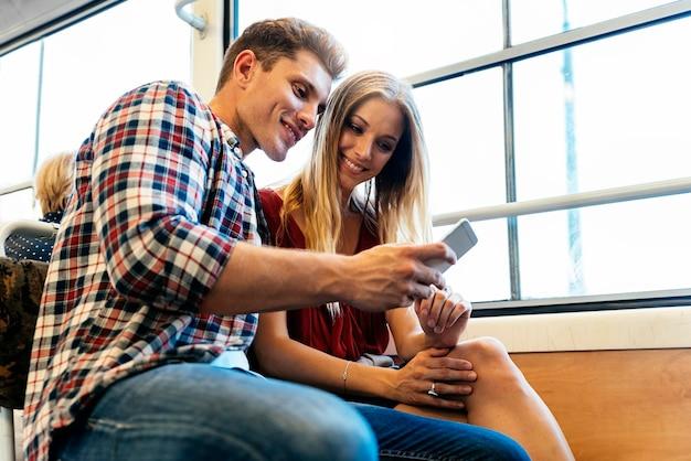 通りで携帯電話を使用して若いカップルの肖像画。モバイルコンセプト。
