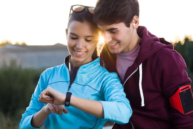 Портрет молодой пары, используя их smartwatch после запуска.