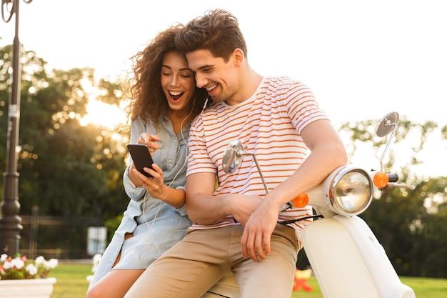 도시 거리에 함께 오토바이에 앉아있는 동안 음악을 듣고 이어폰을 착용하는 젊은 부부의 초상화
