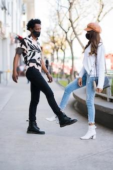 保護マスクを着用し、屋外に立っているときに挨拶するために足をぶつけて若いカップルの肖像画。新しい通常のライフスタイルのコンセプト。