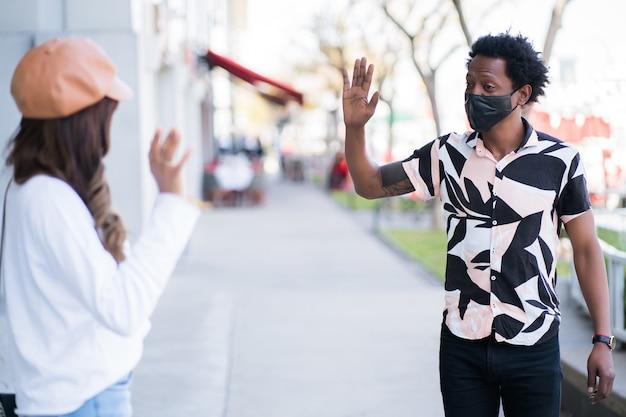 保護マスクを着用し、お互いに挨拶するために手を振っている間距離を保つ若いカップルの肖像画。新しい通常のライフスタイルのコンセプト。