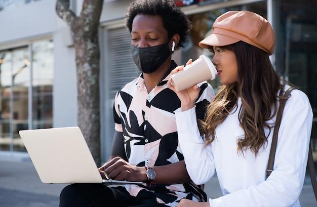 보호 마스크를 착용하고 거리에서 야외에서 노트북을 사용하는 젊은 부부의 초상화