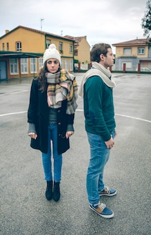 Портрет молодой пары в зимней одежде, стоя на открытом воздухе в холодный и дождливый день