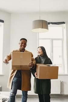 Портрет молодой пары с картонными коробками в новом доме, концепция переезда.