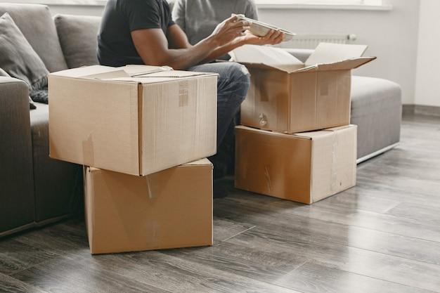 新しい家で段ボール箱を持つ若いカップルの肖像画、家のコンセプトを移動します。