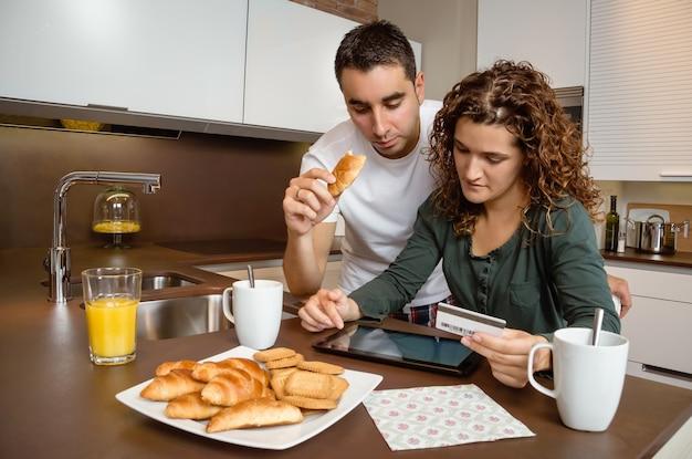 インターネットで電子タブレットとクレジットカードを購入する若いカップルの肖像画。オンラインショッピングのコンセプト。