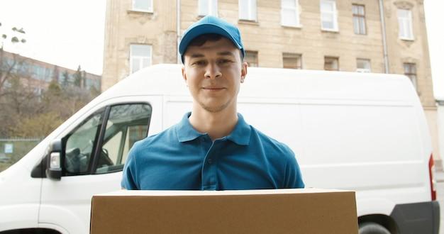 Портрет молодого курьера в маске стоя возле подающей машины и держа картонную коробку